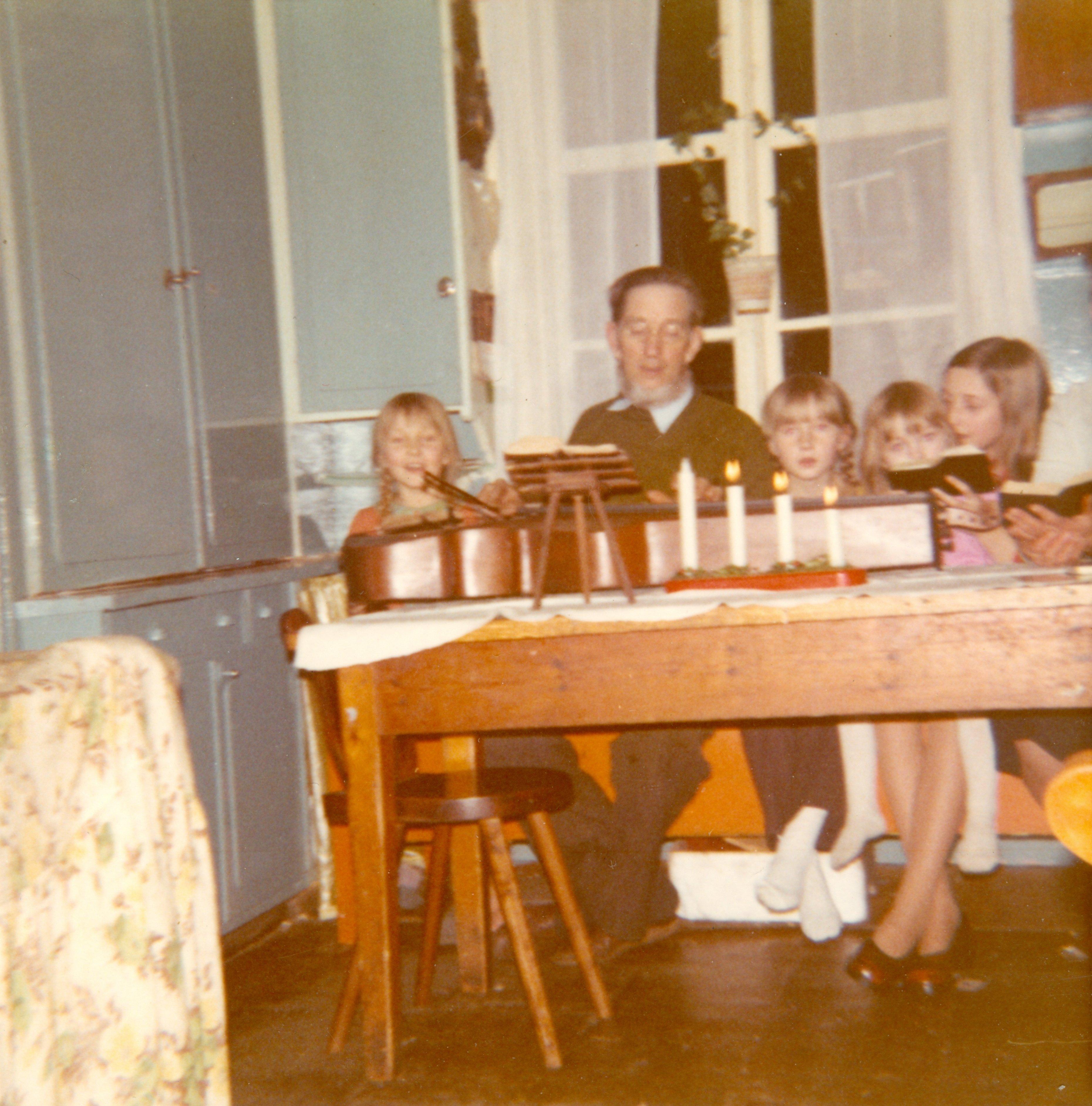 Till höger om far som spelar psalmodikon. Det hände rätt ofta att far flätade våra långa hår.